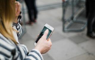Kvinna håller en mobiltelefon